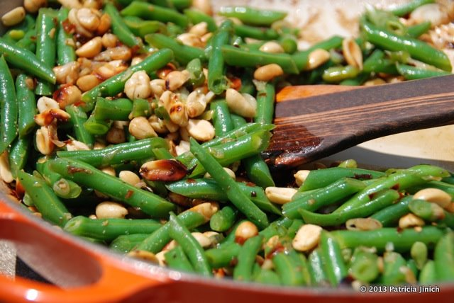 Green beans with peanuts and chile de arbol in pan with wooden spoon