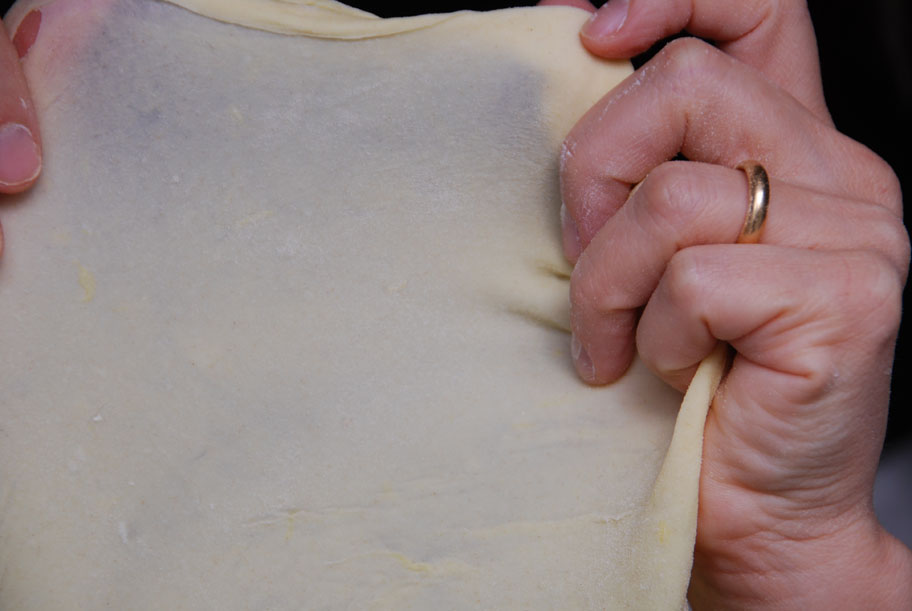 stretching bunuelos dough